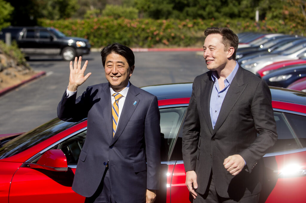 Japanese Prime Minister Shinzo Abe stands with Tesla CEO Elon Musk after returning from a brief test ride at Tesla's headquarters in Palo Alto, Calif., Thursday, April 30, 2015. (AP Photo/Noah Berger)